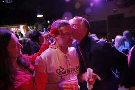 """Gentle Blythe, left, places a flower on Eric Jansen's ear as his partner Maurice Kelly kisses him as Jansen and co-host Marilyn Pittman celebrate the tenth anniversary taping of their radio show """"Out in the Bay"""" at the Oasis nightclub in San Francisco, Calif., on Wednesday, April 29, 2015."""