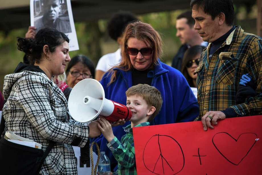 A protester hands a young child the megaphone during a protest against police brutality at Westlake Center on Wednesday, April 29, 2015. On this day, people gathered in cities across the nation including New York, Boston and Minneapolis to support Baltimore in demanding justice and reform after the death of Freddie Gray. Photo: DANIELLA BECCARIA, SEATTLEPI.COM / SEATTLEPI.COM