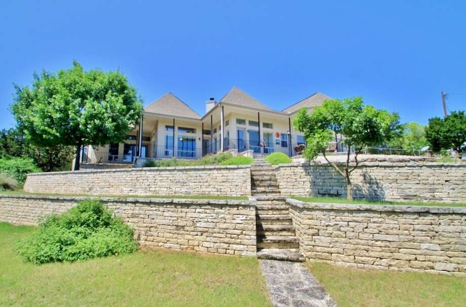 Address: 1119 OC Trout Drive, Canyon Lake, TX 78133  Size: 2,385 sq.ft.   Bedrooms: 3   Bathrooms: 2.5   Year built: 1997   Acreage: .44 acres   Neighborhood/HOA: Triple Peak Ranch Estates, voluntary   Amenities: Gorgeous one-story lake home in immaculate condition! Expansive lake views, 748 sq.ft. of covered patio, gourmet island kitchen with $13,000 in GE Monogram appliances, induction cooktop and granite counters, formal dining, stone fireplace, Hunter Douglas blinds, large mudroom with storage, master retreat with luxury bath and no-step walk-in shower. GE GeoSpring high-efficiency water heater, low-maintenance brick exterior with aluminum fascia/soffit, 40-year high-impact roof, stone storage building, boat storage and extra parking. Photo: Courtesy