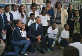 President Obama poses with students after speaking at a live virtual field trip with students from around the country at the Anacostia Library on April 30 in Washington, D.C.