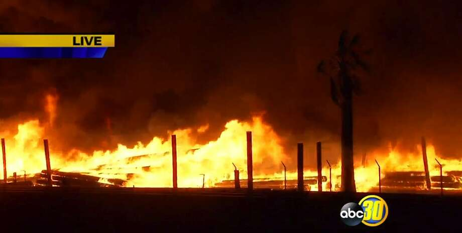 This frame grab from video provided by ABC30-KFSN-TV Fresno,  several power poles are burn early Thursday, April 30, 2015 in Fresno, Calif.  KFSN-TV reports the blaze was reported before dawn Thursday along State Route 99 northwest of downtown. Firefighters say there is a lot of fuel for the fire, but a lack of hydrants in the area, making it difficult to fight the blaze. Photo: Associated Press