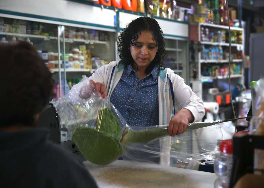 Gladys Alvarez works as a cashier at the Casa Lucas grocery store on 24th Street in San Francisco, Calif. on Thursday, April 30, 2015. Alvarez is looking forward to a modest bump in her paycheck when the hourly minimum wage in the city increases to $12.25 on Friday. Photo: Paul Chinn, The Chronicle