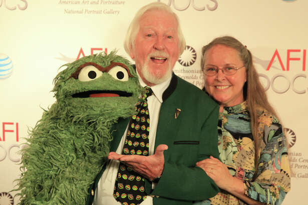 Caroll Spinney holds his Muppet character Oscar the Grouch alongside his wife, Debra.