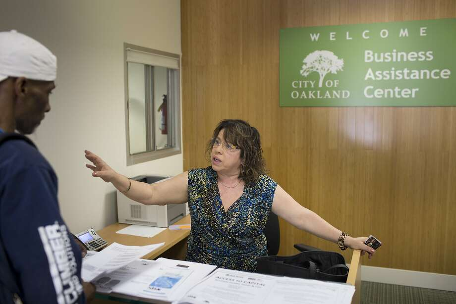 Susana Villareal helps Hal Hubbard at Oakland's Business Assistance Center in Oakland, Calif. on Thursday, April 30, 2015. Many businesses are still unaware or not in compliance of the wage increase, and a system to enforce the new law is still absent. Villareal helps inform businesses and help them make the transition. Photo: Tim Hussin, Special To The Chronicle