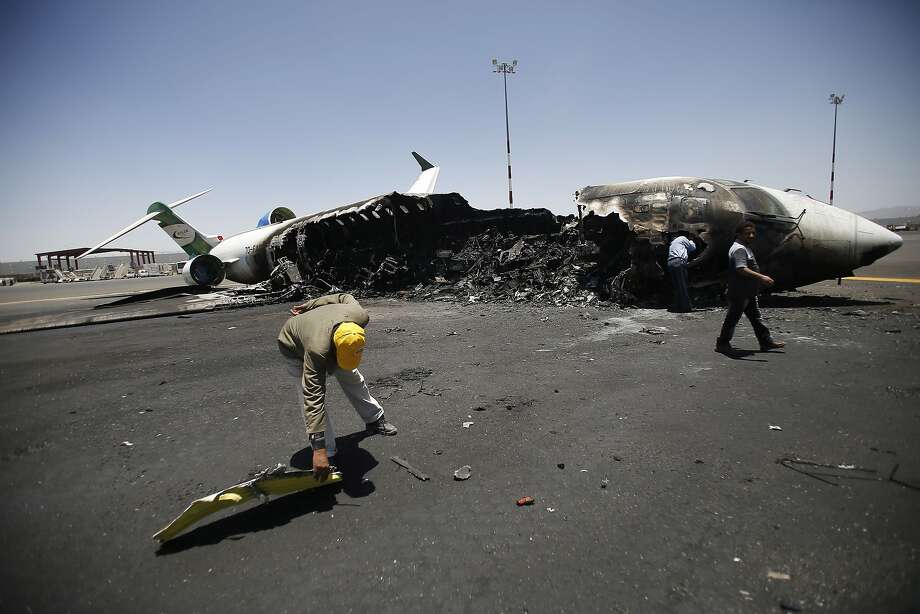 Officials of Felix Airways, a domestic airline, inspect a plane destroyed by Saudi-led airstrikes, at the Sanaa International airport, in Yemen, Wednesday, April 29, 2015. Saudi-led coalition warplanes pounded Shiite rebels and their allies overnight and throughout the day on Tuesday in the Yemeni capital. Around midday, airstrikes hit Sanaa International airport, setting a plane owned by a private company on fire, according to a statement released by the Shiite rebels, known as Houthis. Photo: Hani Mohammed, Associated Press