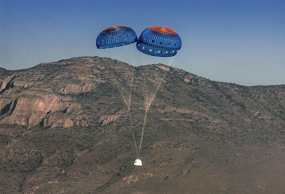 Blue Origin's New Shepard crew capsule descends by parachute in the west Texas desert. Photo: Associated Press