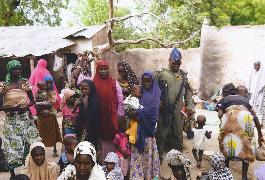 A soldier stands next to women and children rescued in an operation against Boko Haram in an undisclosed location near the group's forest stronghold. Photo: -, AFP / Getty Images