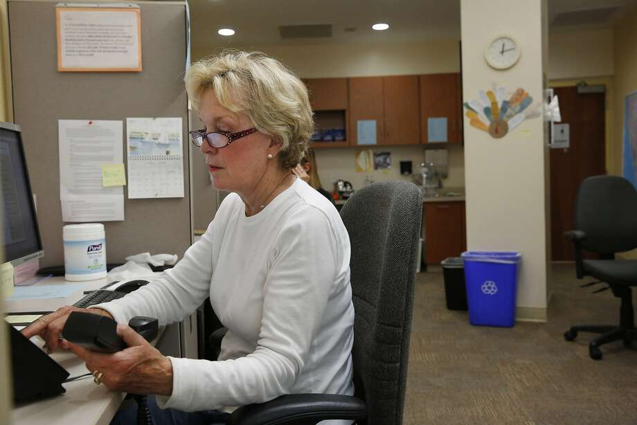 Volunteer counselor Lynn Elwell dials a client on the phone in the Friendship Line office at the Institute on Aging April 30, 2015 in San Francisco, Calif. Elwell has been volunteering for seven years with the line after she retired from her counseling work. The warm line, which is a 40-year-old program, is run through the Institute on Aging's Center for Elderly Suicide Prevention and Grief-Related Services provides crisis intervention. Counselors provide well-being check-ins, medical reminders and emotional support to anyone who calls in. Photo: Leah Millis, The Chronicle