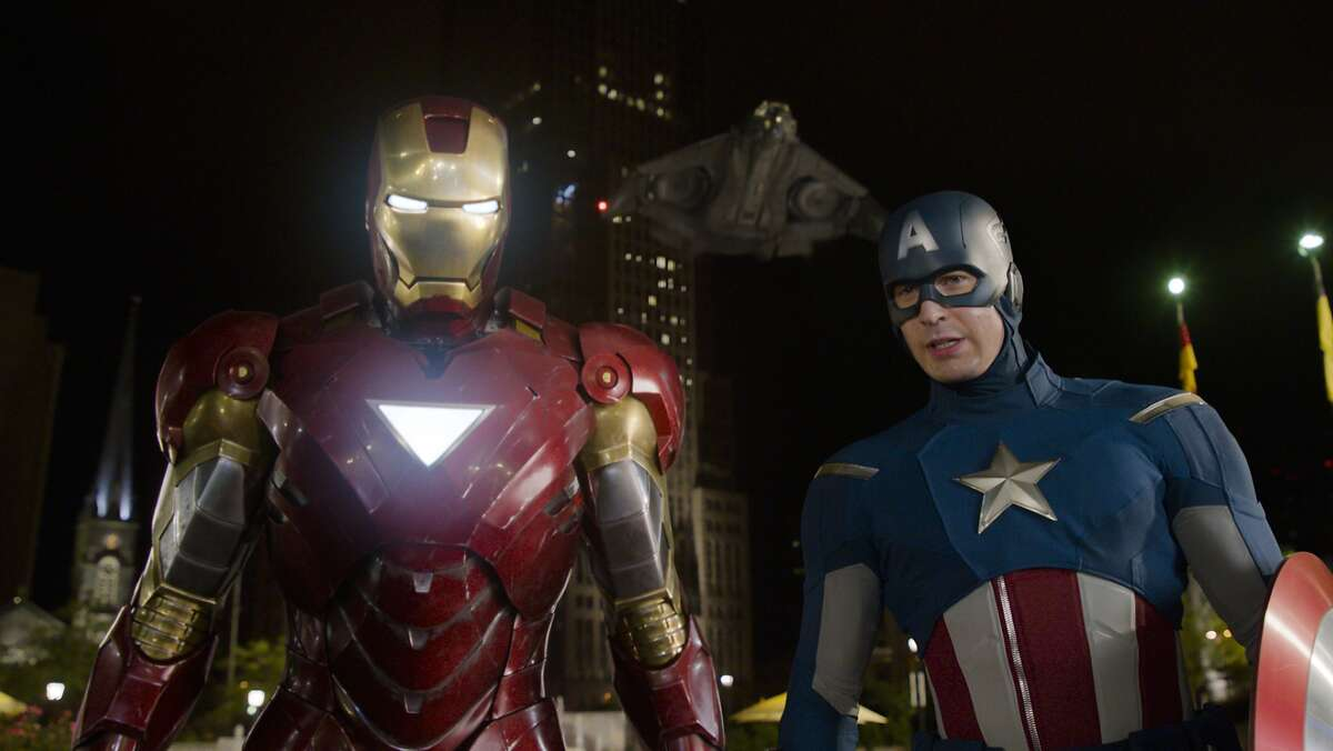 This film image released by Disney shows, Iron Man, portrayed by Robert Downey Jr., left, and Captain America, portrayed by Chris Evans, in a scene from