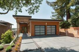 The Oakland Hills home features clean lines, a covered entryway and a stamped concrete driveway.