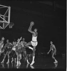 Wilt Chamberlain takes a shot over Hawks defenders.
