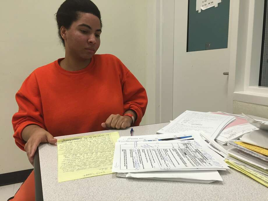 """Tyqwon Welch, 25, looks over court documents in her attempted murder case from inside San Francisco County Jail. She is accused of trying to burn down her plastic surgeon's home -- the """"Mrs. Doubtfire"""" house in San Francisco -- on Jan. 5. Photo: Evan Sernoffsky"""