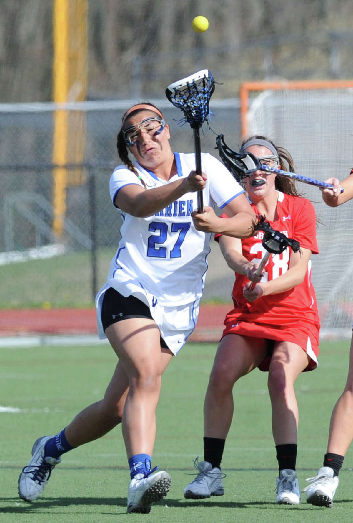 At left, Darien's Gabby Noto (#27) goes for a loose ball against Clare Loughran (#28) of Greenwich, right, during the girls high school lacrosse match between Darien High School and Greenwich High School at Darien, Conn., Thursday, April 30, 2015. Darien defeated Greenwich, 20-10.