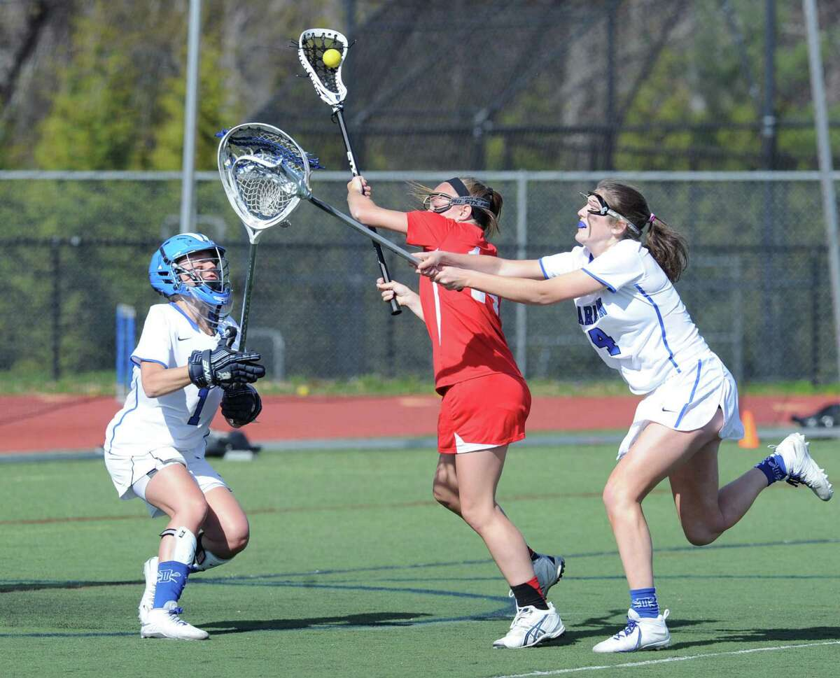 At center, Anne Dunster of Greenwich makes a move on Darien goalie Sammy Nielsen, left, before scoring a goal during the girls high school lacrosse match between Darien High School and Greenwich High School at Darien, Conn., Thursday, April 30, 2015. Trailing the play is Elizabeth Fucigna (#4) of Darien. Darien defeated Greenwich, 20-10.