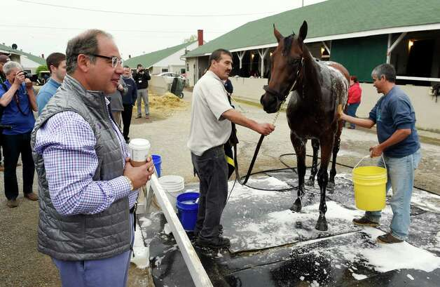 Owner Ahmed Zayat, left, watches his morning line favorite American Pharaoh get his bath after morning exercise Thursday morning April 30, 2015,  just two days before the 141st Kentucky Derby at Churchill Downs in Louisville, Kentucky.       (Skip Dickstein/Times Union) Photo: SKIP DICKSTEIN