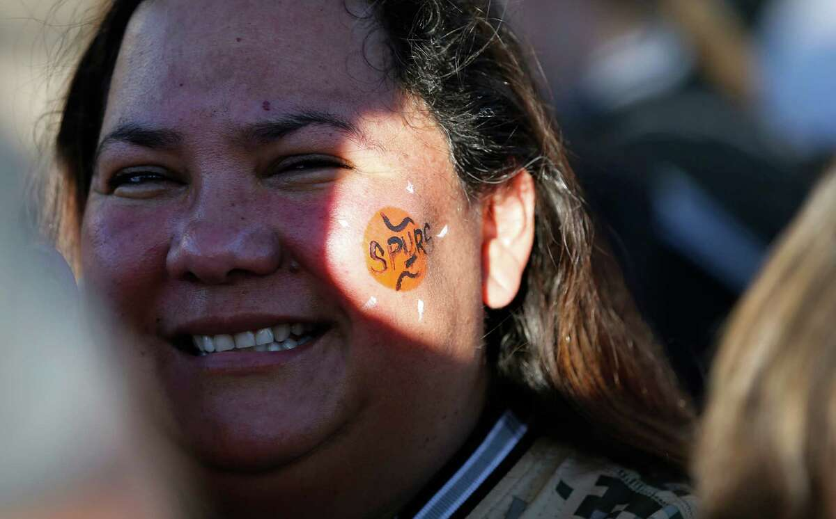 Spurs fan Lisa Johnson gets a Spurs decoration painted on her cheek before Game 6 between the Spurs and the Los Angeles Clippers in the first round of the Western Conference playoffs at the AT&T Center on Thursday, Apr. 30, 2015.