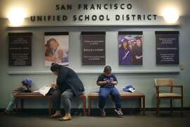 Carolina Rodas (center) fills out a San Francisco Unified School District  application for her son Maifala Rodas (right) as niece Camila Rodas (left), 2 draws next to her on the last day to hand in applications for round 1 for the upcoming school year  on Friday, January 16, 2015 in San Francisco, Calif.