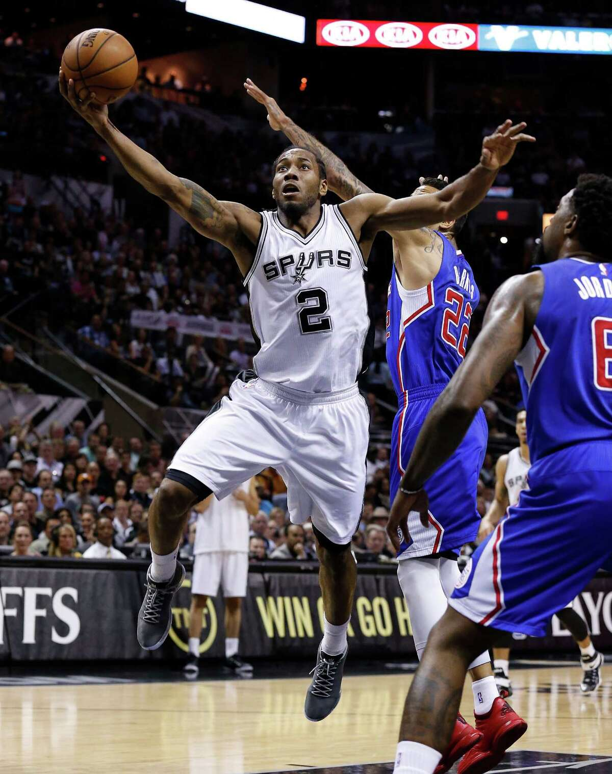 Spurs' Kawhi Leonard (02) goes in for layup against Los Angeles Clippers' Matt Barnes (22) during Game 6 of the first round of the Western Conference playoffs at the AT&T Center on Thursday, Apr. 30, 2015.