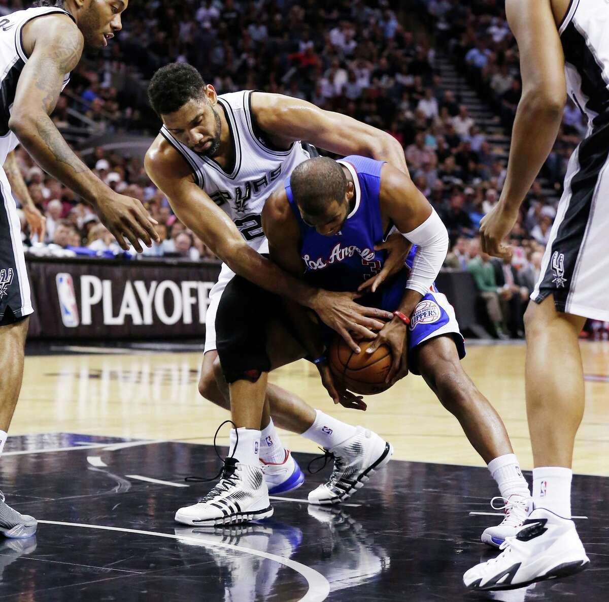 Spurs' Tim Duncan (21) ties up Los Angeles Clippers' Chris Paul (03) for a loose ball during Game 6 of the first round of the Western Conference playoffs at the AT&T Center on Thursday, Apr. 30, 2015.