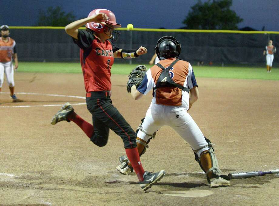 Raeven Trevino of New Braunfels Canyon scores as Madison catcher Megan Shuey waits for the ball during UIL Class 6A playoffs action at Steele High School on April 30, 2015. Photo: Billy Calzada /San Antonio Express-News / San Antonio Express-News