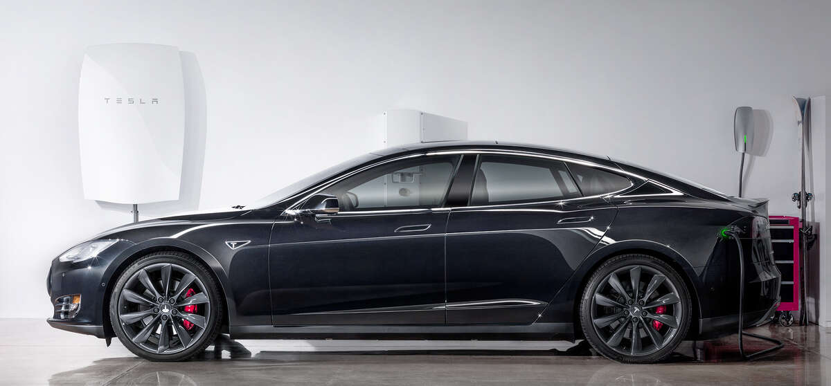 Tesla's new home-based battery, the Powerwall, shown with the company's Model S electric sedan.