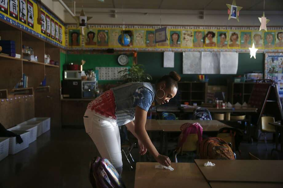 "Keana Shepard-Gardner cleans kindergarten classroom tables in her daughter's classroom as the students play during recess in San Francisco. School board members across the state have banded together against a state law that limits the amount of money districts can set aside for a rainy day, saying the cap is ""fiscally reckless"" and ties the hands of local officials. Photo: Lea Suzuki, The Chronicle"
