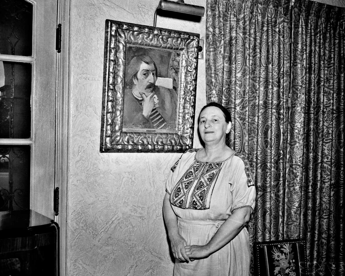 """Marion Koogler McNay in her home with her 1893 oilpainting by Paul Gauguin, """"Portrait of the Artist with the Idol."""""""