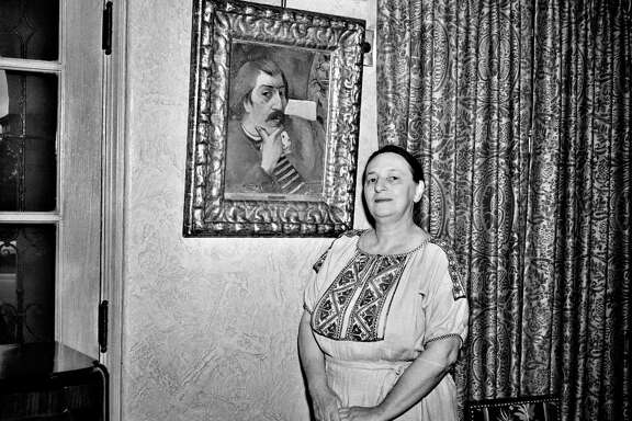 "Marion Koogler McNay in her home with her 1893 oilpainting by Paul Gauguin, ""Portrait of the Artist with the Idol."""