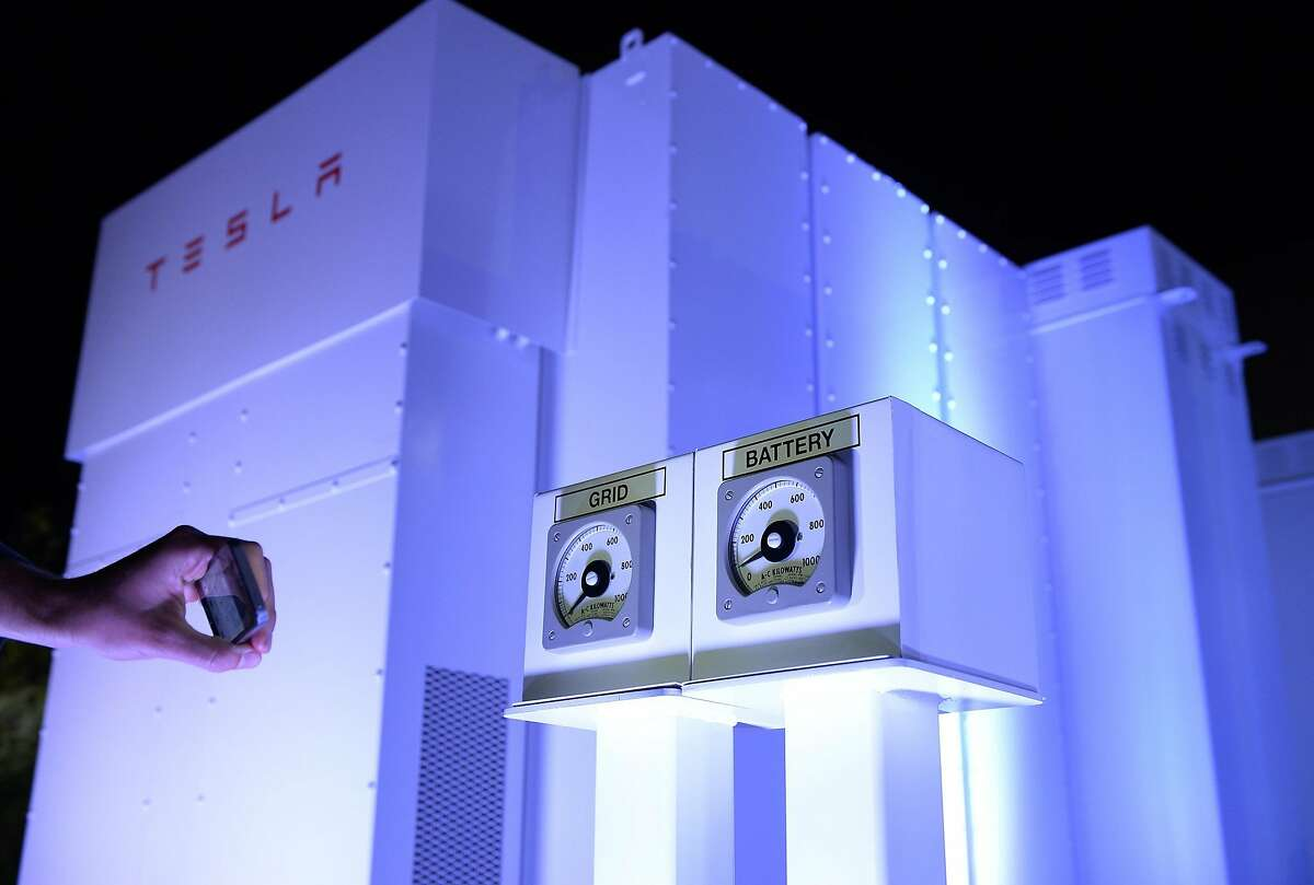 A guests takes photographs of the Powerpack system after Elon Musk, CEO of Tesla unveiled suit of batteries for homes, businesses, and utilities at Tesla Design Studio April 30, 2015 in Hawthorne, California. Musk unveiled the home battery named Powerwall with a selling price of $3500 for 10kWh and $3000 for 7kWh and very large utility pack called Powerpack. (Photo by Kevork Djansezian/Getty Images)