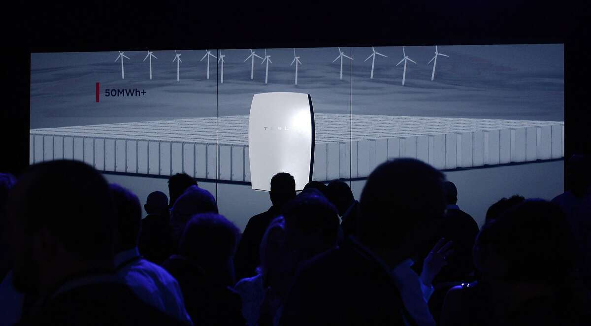 LOS ANGELES, CA - APRIL 30: Guests look at a Powerwall system on display after Elon Musk, CEO of Tesla unveiled suit of batteries for homes, businesses, and utilities at Tesla Design Studio April 30, 2015 in Hawthorne, California. Musk unveiled the home battery named Powerwall with a selling price of $3500 for 10kWh and $3000 for 7kWh and very large utility pack called Powerpack. (Photo by Kevork Djansezian/Getty Images)