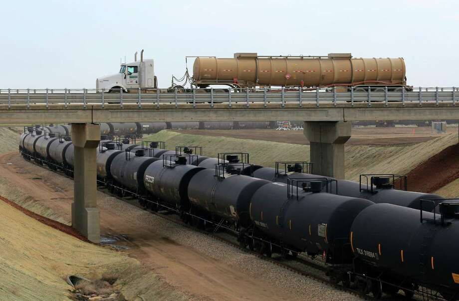 A tanker truck leaves an oil shipping depot, passing over a string of tankers on a rail line, in New Town, N.D. Not having Keystone XL built means railroads will get to keep much of the business they're already hauling and compete for new production as it comes online. Photo: New York Times File Photo / NYTNS