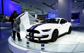 Workers cover up a Ford Mustang Shelby GT350 as they prepare for The North American International Automobile Show in Detroit on January 10, 2015. Some 20 manufacturers will compete for the spotlight in a US market that has been a bright spot in a world where other economies are struggling to grow. The Automobile Show expects a million visitors to descend on bone-chilling Detroit between January 17 and 25. AFP PHOTO/JEWEL SAMAD        (Photo credit should read JEWEL SAMAD/AFP/Getty Images)