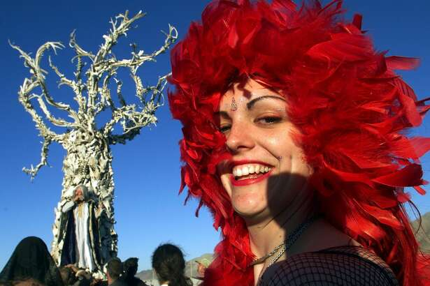 """BLACK ROCK CITY, UNITED STATES:  A woman walks near the """"Tree of Time"""", a sculpture by San Francisco-based artists Dana and Flash, at Black Rock City's Burning Man festival in Nevada 04 September 1999. Founded in 1986 by a group of fine artists, filmmakers and photographers, the annual event encourages a collaborative response from it's audience and a collaboration between artists. (ELECTRONIC IMAGE) AFP PHOTO / Hector MATA"""
