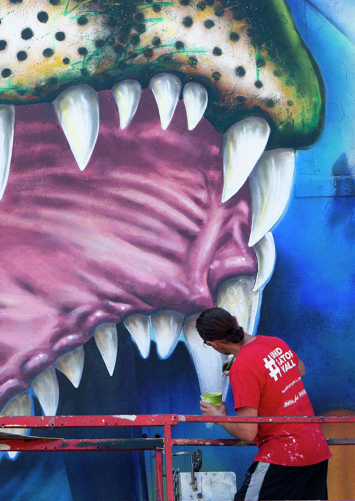"""Artist Sebastien """"Mr. D"""" Boileau works on his mural depicting, Ed-U-Gator, the University of Houston-Downtown's mascot, Friday, May 1, 2015, in Houston. The mural will reside on the north side of a storage facility on campus."""