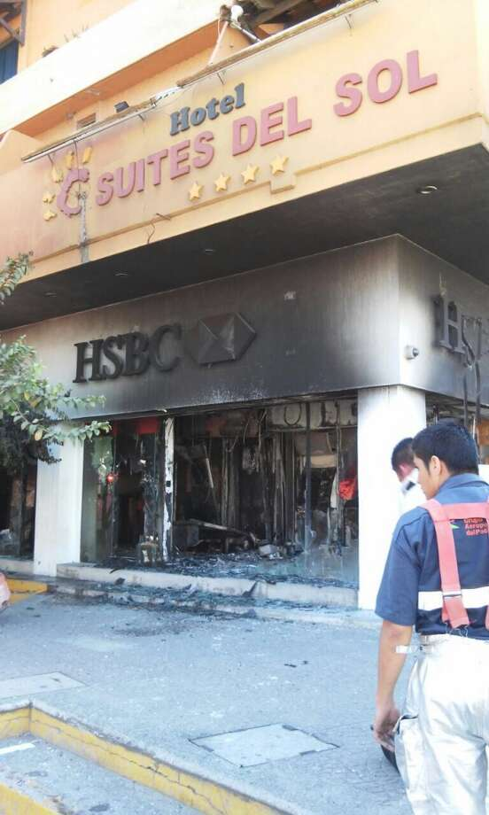 Firefighters work to put out a fire in a bank in Puerto Vallarta, Jalisco state, Mexico, on May 1, 2015. Criminals burnt simultaneously several robbed vehicles to block at least four accesses to Guadalajara, the second largest city of Mexico, informed authorities of the state of Jalisco. In Puerto Vallarta 15 criminals burned gas stations and 4 banks. AFP PHOTO/Moisés Madariaga/ Diario MeridianoHECTOR GUERRERO/AFP/Getty Images Photo: AFP / Getty Images