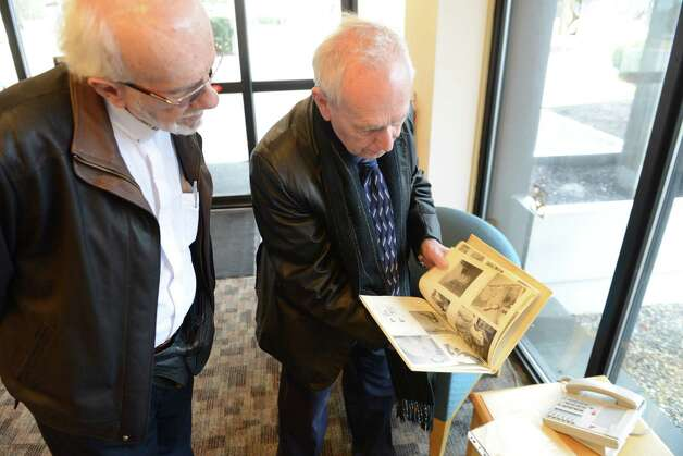 Rev. Richard La Corte, left, and Albert La Pointe, right, look through a 1971 yearbook from when they worked to together in the Virgin Islands Friday, April 10, 2015, at the Times union in Colonie, N.Y.  The two men taught together in the Virgin Islands many years ago and had not seen each other since then. (Will Waldron/Times Union) Photo: WW / 00031386A