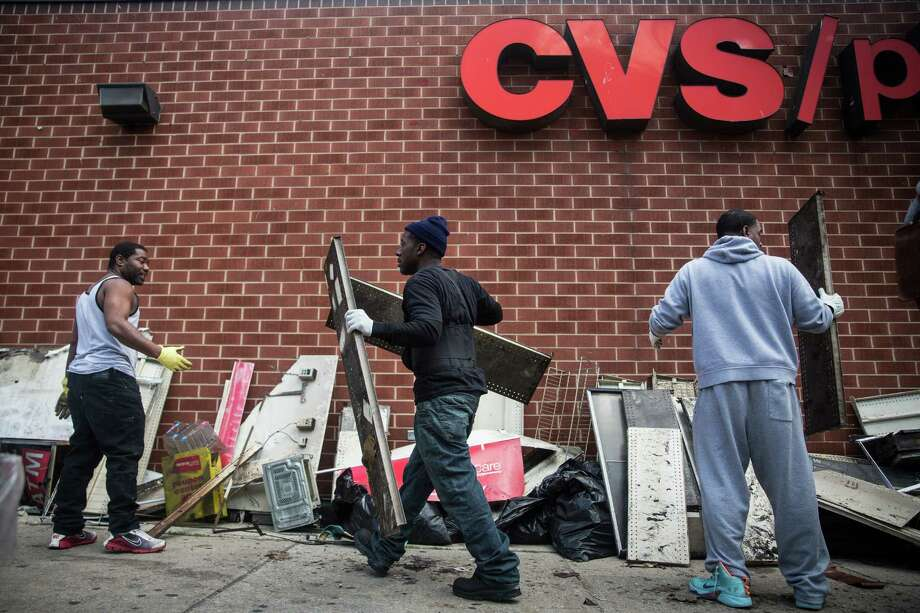 Volunteers help clean up debris from a CVS pharmacy that was set on fire during rioting in Maryland that followed the death of Freddie Gray. A reader sees no excuse for the rioting. Photo: Andrew Burton /Getty Images / 2015 Getty Images