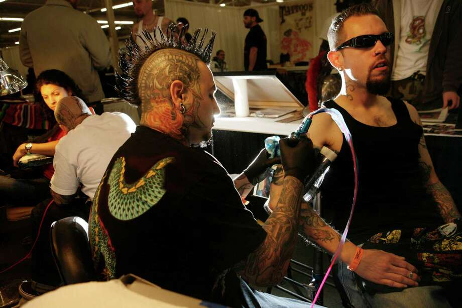Tattoo artist Roman from Artistic Element tattoo shop in Yucaipa, Calif. works on an arm tattoo for Brandon Bracamont, of Sacramento, Calif. at the annual Tattoo and Body Art Expo at the Cow Palace on Friday, March 28, 2008 in Daly City , Calif.  Photo by Mike Kepka / San Francisco Chronicle Photo: Mike Kepka, Chronicle Staff Photographer / ONLINE_YES