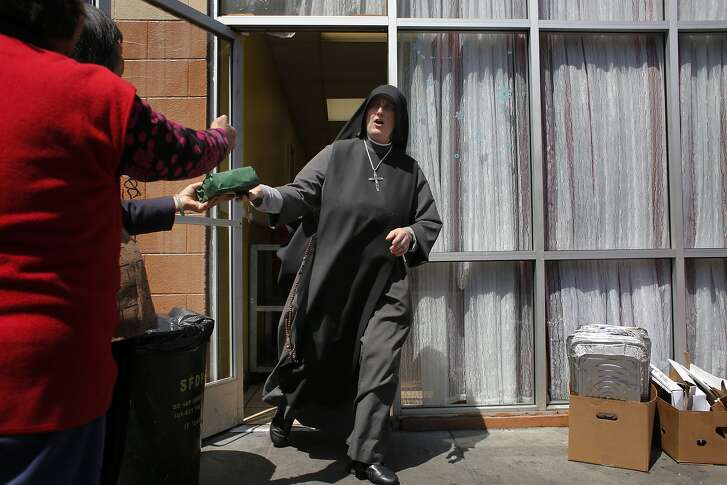 Rushing off to an appointment, Sister Mary Benedicte hands off a sandwich to latecomers at the Fraternite Notre Dame Mary of Nazareth Soup Kitchen on Turk Street in San Francisco, Calif.