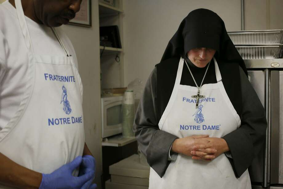 Moments before the doors open for lunch, Sister Mary Benedicte leads her volunteer staff in prayer in the kitchen at the Fraternite Notre Dame Mary of Nazareth Soup Kitchen on Turk Street in San Francisco, Calif. Photo: Mike Kepka, The Chronicle