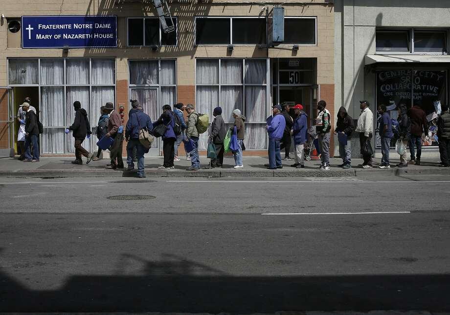 Tenderloin locals line up for a meal outside the Fraternite Notre Dame Mary of Nazareth Soup Kitchen on Turk Street in San Francisco, Calif. Photo: Mike Kepka, The Chronicle