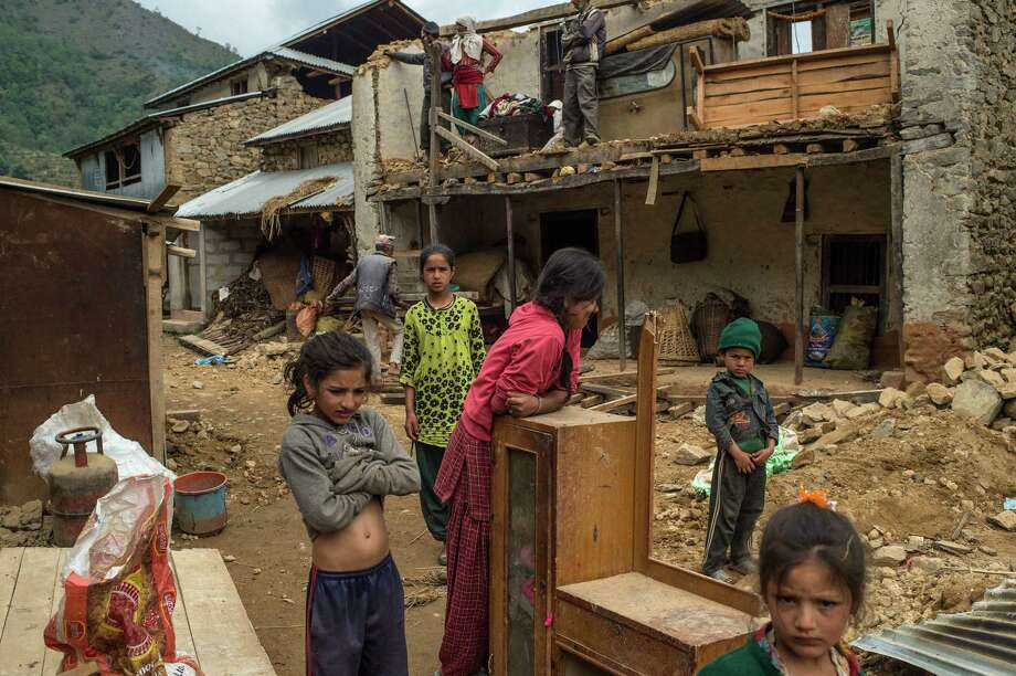 BHOTECHAUR, NEPAL - MAY 01:  Members of the Ghomenath Chaulagain family work on the resconstruction of their family home on May 1, 2015 in Bhotechaur, Nepal. A major 7.8 earthquake hit Kathmandu mid-day on Saturday, and was followed by multiple aftershocks that triggered avalanches on Mt. Everest which buried mountain climbers in their base camps. Many houses, buildings and temples in the capital were destroyed during the earthquake, leaving over 6000 dead and many more trapped under the debris as emergency rescue workers attempt to clear debris and find survivors. Regular aftershocks have hampered recovery missions as locals, officials and aid workers attempt to recover bodies from the rubble.  (Photo by David Ramos/Getty Images) *** BESTPIX *** Photo: David Ramos, Stringer / 2015 Getty Images