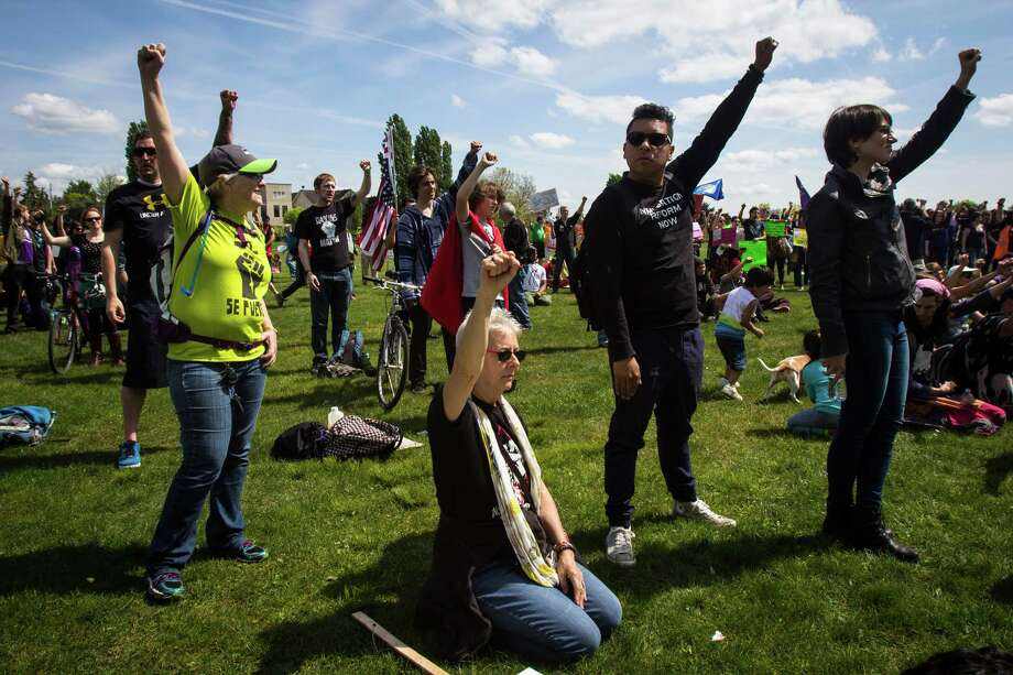 "Protesters hold up their fists during a protest at Judkins Park. The peaceful march had many asking for immigration reform and an end to police brutality. A later unruly march in Capitol Hill was described by police as a ""riot. Photographed on May 1, 2015. Photo: DANIELLA BECCARIA, SEATTLEPI.COM / SEATTLEPI.COM"