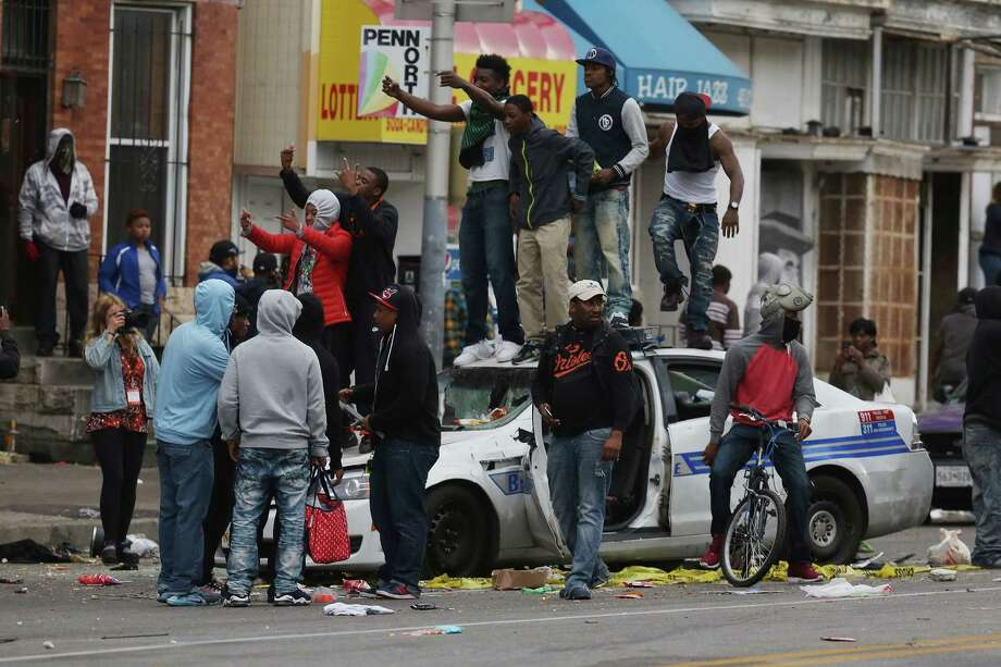 BALTIMORE, MD - APRIL 27:  Demonstrators climb on a destroyed Baltimore Police car in the street near the corner of Pennsylvania and North avenues during violent protests following the funeral of Freddie Gray April 27, 2015 in Baltimore, Maryland. Gray, 25, who was arrested for possessing a switch blade knife April 12 outside the Gilmor Homes housing project on Baltimore's west side. According to his attorney, Gray died a week later in the hospital from a severe spinal cord injury he received while in police custody.  (Photo by Chip Somodevilla/Getty Images) Photo: Chip Somodevilla, Staff / 2015 Getty Images