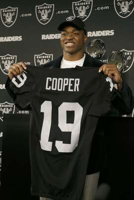 Wide receiver Amari Cooper, the first round draft pick of the Oakland Raiders, holds up a jersey after a news conference in Alameda, Calif., Friday, May 1, 2015. (AP Photo/Jeff Chiu)