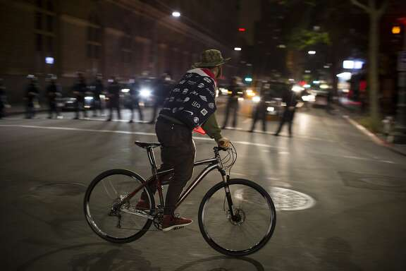 A protester rides by police during a May Day protest in Oakland, Calif. on Friday, May 1, 2015.
