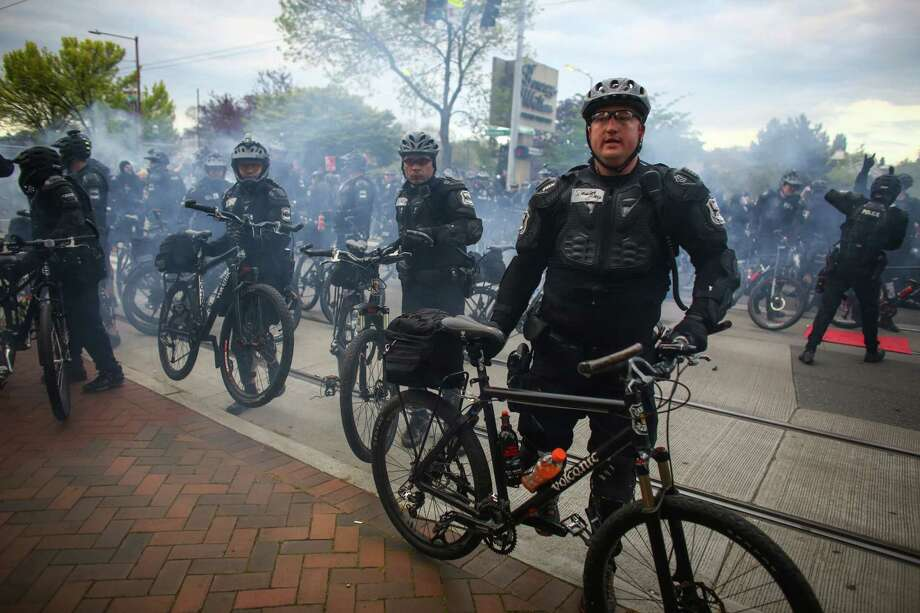 "Police push back the crowd during an anti-capitalist and anti-police brutality march in Seattle. Police described the march as a ""riot"" after marchers there objects at officers, broke windows and police responded to the rowdiness with pepper spray, crowd dispersal grenades and pepper balls. A march earlier in the day for immigrant and worker rights was peaceful. Photographed on May 1, 2015. Photo: JOSHUA TRUJILLO, SEATTLEPI.COM / SEATTLEPI.COM"