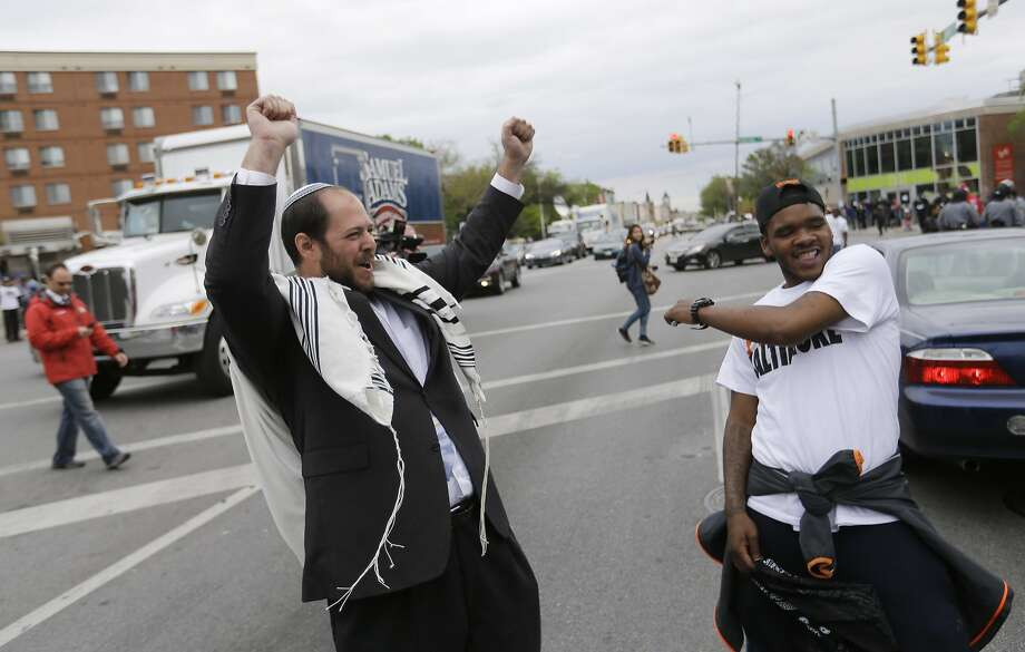 Rabbi Yerachmiel Shapiro, left, and Meach Johnson celebrate on Friday, May 1, 2015, after State's Attorney Marilyn J. Mosby announced criminal charges against all six officers suspended after Freddie Gray suffered a fatal spinal injury while in police custody in Baltimore. Mosby announced the stiffest charge, second-degree depraved heart murder, against the driver of the police van. Other officers faced charges of involuntary manslaughter, assault and illegal arrest. Photo: David Goldman, Associated Press