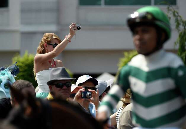 A woman makes a photo of the horses going to the track during the undercard this afternoon May 2, 2015 at Churchill Downs in Louisville, Kentucky.  The 141st running of the Kentucky Derby post time is 6:34 this evening.    (Skip Dickstein/Times Union) Photo: SKIP DICKSTEIN