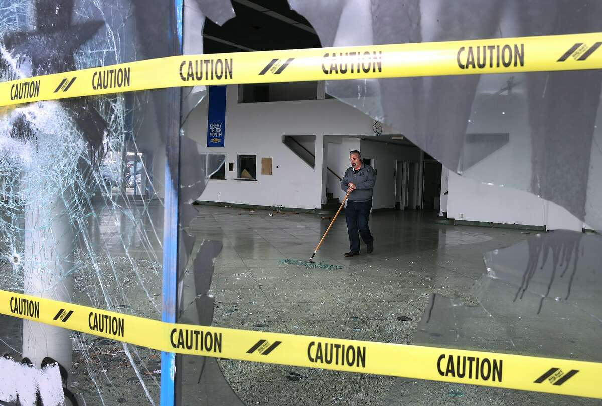 Steve Tittel sweeps broken glass from inside the vacant GM Auto Mall showroom in Oakland, Calif. on Saturday, May 2, 2015 after a demonstration turned violent Friday night. More than 40 new cars parked in a dealership storage lot adjacent to the showroom were heavily damaged or destroyed and windows were smashed at several businesses along the Broadway corridor.